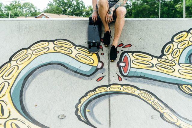 Skateboarder against a squid mural